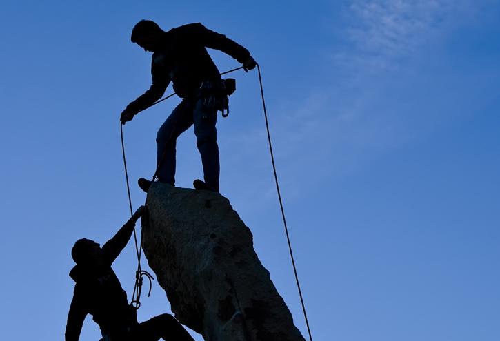 Team of climbers reaching the summit.