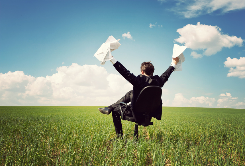 businessman sitting on a chair in a field and holding documents