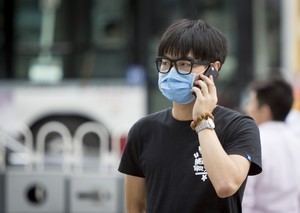 Beijing, China - August 4, 2014: Young man is wearing a mask because of the air pollution in China's capital Beijing.