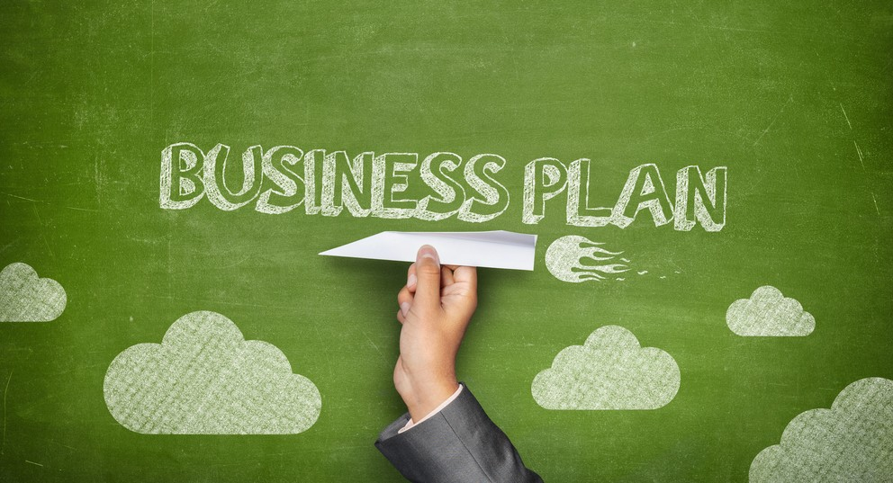 Business plan concept on green blackboard with businessman hand holding paper plane