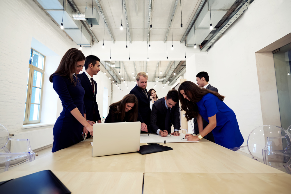 Successful multi ethnic group of architects dressed in luxury corporate clothes working together during briefing, young professional engineers reviewing blueprints while standing in office interior